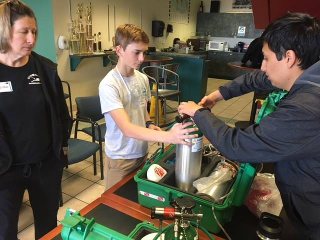 Trent works with Mr. Alaniz at the oxygen station.